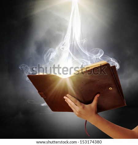 Human hand holding magic book with magic lights - stock photo