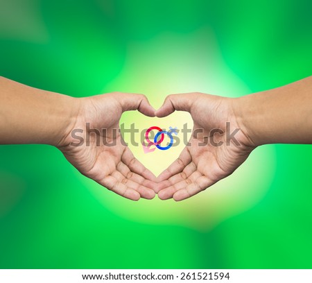 Human hand holding Mars Venus or Male Female symbol. Safe Sex concept. - stock photo