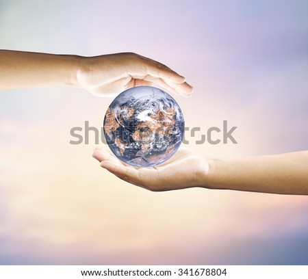 Human hand holding medium green plant with soil on blurred abstract. Ecology, World Environment, Tree of Knowledge concept.Elements of image (like cloud map, world map, etc) are furnished by NASA - stock photo