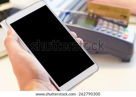 Human Hand Holding Mobile Phone With Credit Card Machine In Background : Selective Focus On Mobile - stock photo