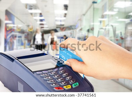 Human hand holding plastic card in payment machine in shop - stock photo