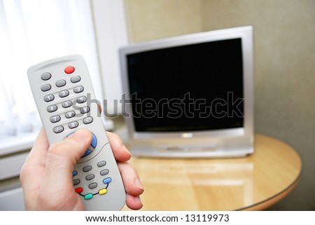 human hand holding remote control against tv