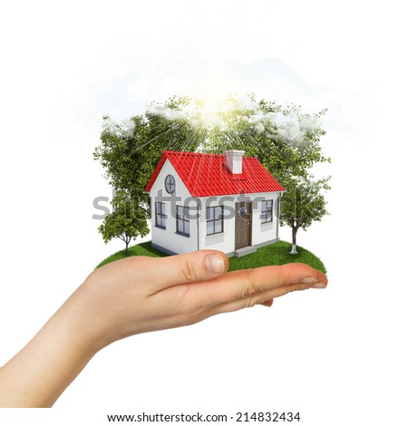 Human hand holding small house with trees and grass - stock photo