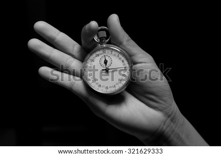 Human hand holding stopwatch (black and white)