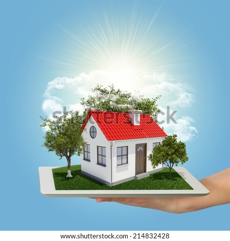 Human hand holding tablet pc with small house and trees - stock photo