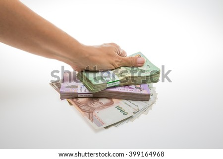 Human hand holding Thai banknotes, isolated on white background.