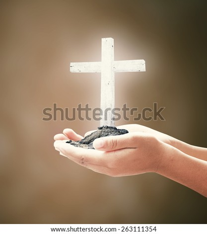 Human hand holding the wooden white cross. - stock photo