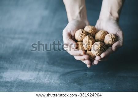 human hand holding walnuts on dark blue background - stock photo