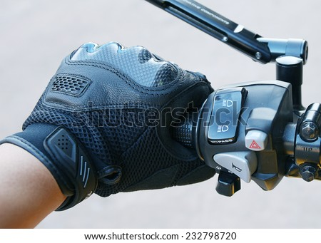 Human hand in a Motorcycle Racing Gloves holds a motorcycle throttle control .Hand protection from accidents. - stock photo