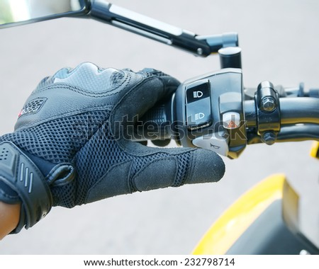 Human hand in a Motorcycle Racing Gloves Press the horn button .Hand protection from accidents. - stock photo