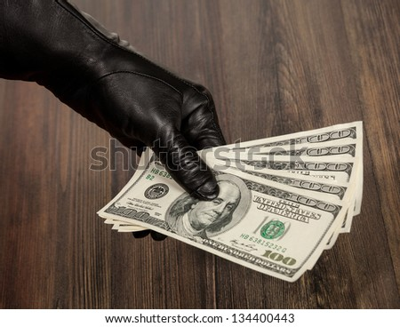 Human hand in black glove holding dollars over a table