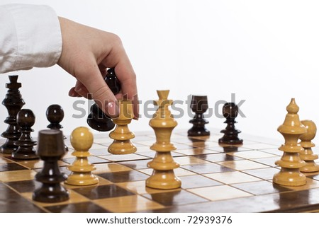 Human hand move chess figure at chessboard.