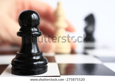 Human hand moves a chess piece on a chess board on a background of a pawn chess piece closeup. - stock photo
