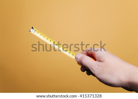 Human hand on a yellow background is holding a tape measure, measure