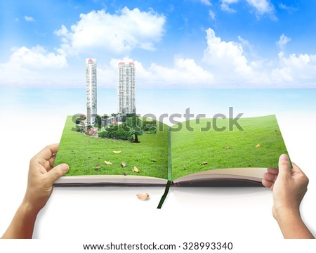 Human hand opening book in the city on meadow over blue sky background. Ecological city World Environment Day CSR Eco Friendly Paper Go Green Earth Hour International Creativity and Innovation concept - stock photo
