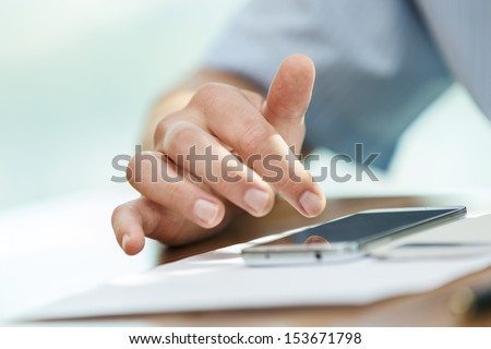 Human hand operating a smartphone gadget  - stock photo