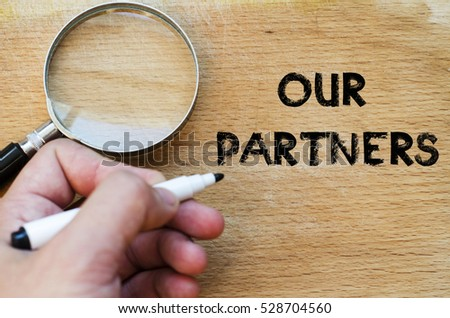 Human hand over wooden background and our partners text concept