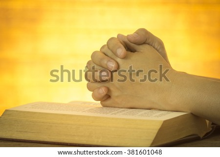 Human hand placed on the Bible, pray to God. - stock photo