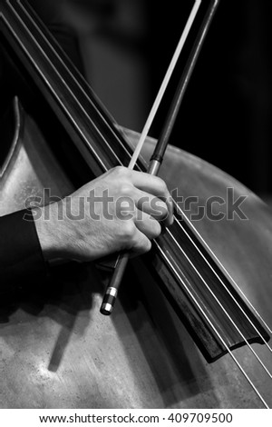 Human Hand playing the contrabass in black and white