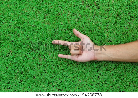 Human hand point with finger on green grass background texture