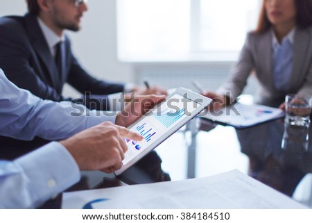 Human hand pointing at touchscreen in working environment at meeting - stock photo