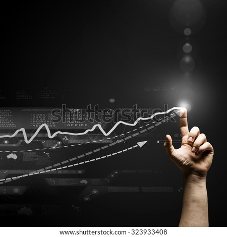 Human hand pointing with finger at growing graph - stock photo