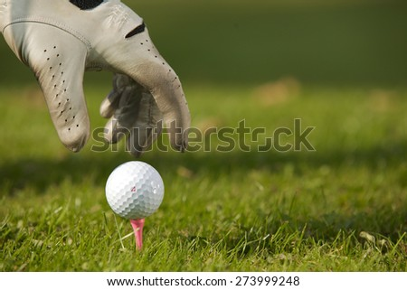 Human hand positioning golf ball on tee, close-up - stock photo