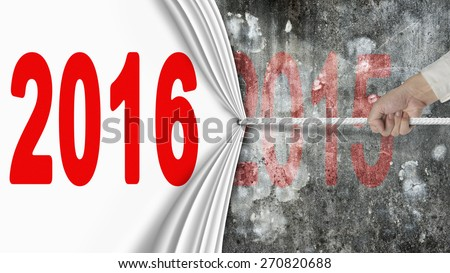 Human hand pulling 2016 white curtain covering dark red 2015 on old mottled concrete wall background - stock photo