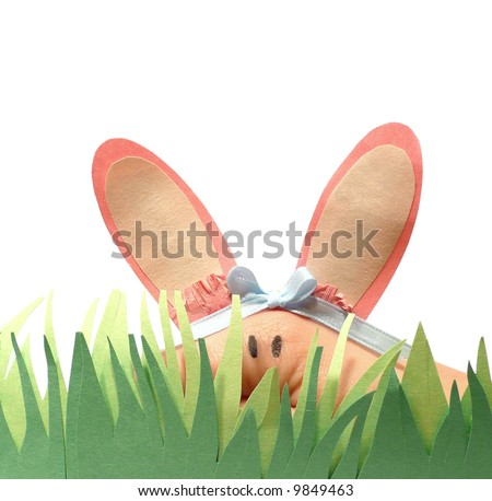 Human hand puppet dressed as the Easter bunny hiding behind paper grass over a white background