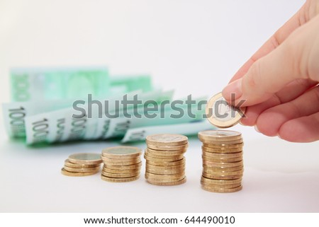 Human hand putting coin to money with euro bills on a background, business ideas