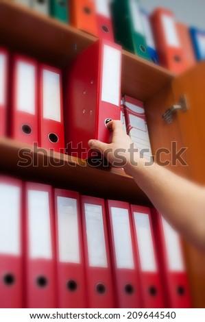 Human hand reaching down to the binder - stock photo
