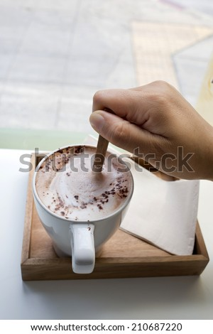 Human hand stir hot chocolate in cafe - stock photo