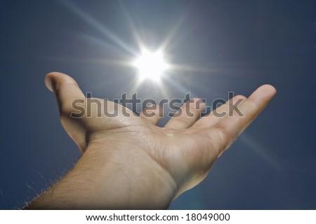 human hand, sun and blue sky - stock photo