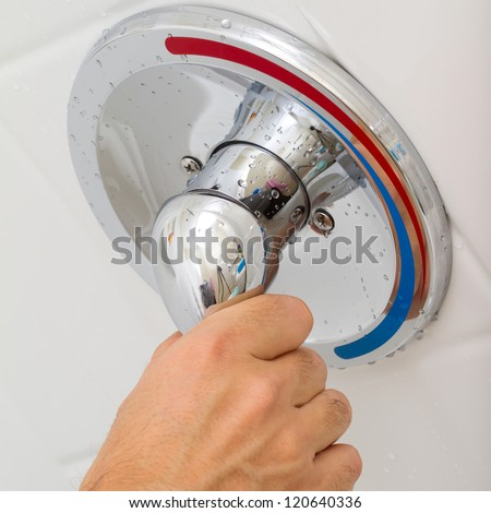Human Hand switches a Shower faucet cold and hot water in the bathroom