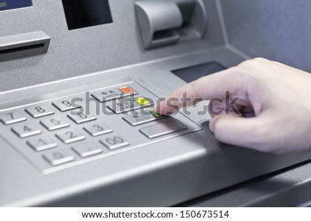 Human hand touching ATM machine