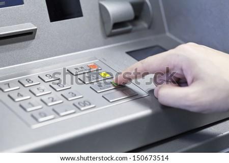 Human hand touching ATM machine - stock photo