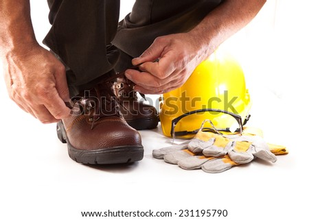 Human hand tying shoelaces on work boots, goggles, gloves and hard hat - stock photo