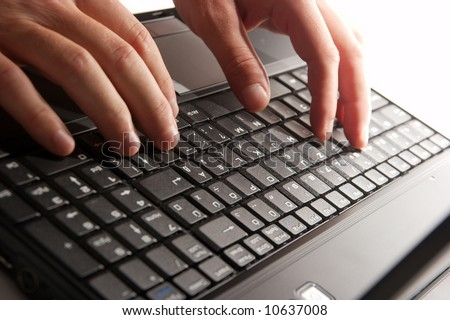 Human hand typing on a laptop