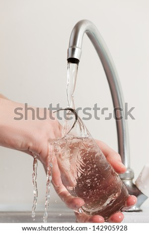 Human hand washing dish or pouring glass with fresh drink water at kitchen faucet - stock photo