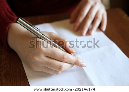 Human hand with a ballpoint pen and a blank sheet of paper.