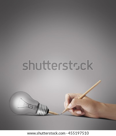 Human hand with a pencil, a pencil, a light bulb on gray creative concepts.