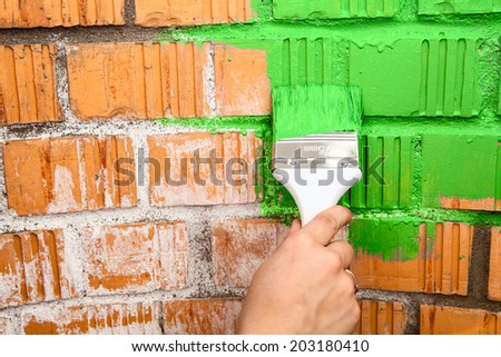 Human hand with green colored brush painting brick wall - stock photo
