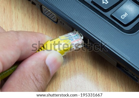 human hand with network cable prepare connect to laptop computer