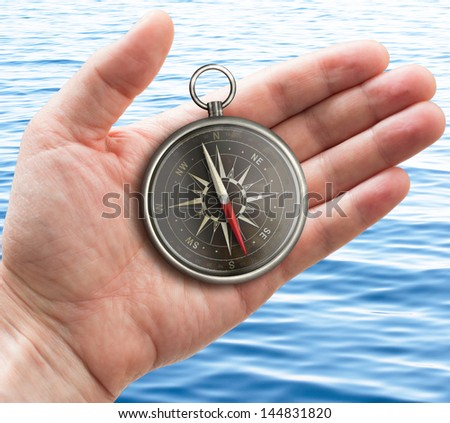 human hand with old pocket compass over sea or ocean surface - stock photo
