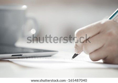 Human hand with pen calculating budget. Teacup and digital tablet on a table - stock photo