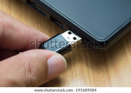 human hand with USB cable prepare connect to laptop computer - stock photo