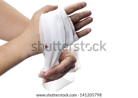 Human hand wrapping white medicine bandage on his hand. - stock photo