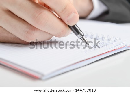 Human hand writing in a notebook