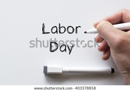 Human hand writing labor day on whiteboard