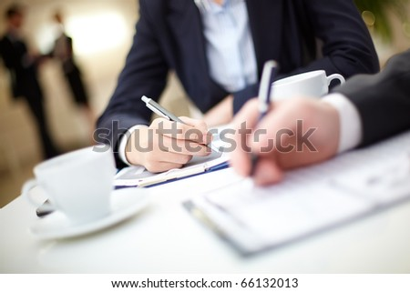 Human hand writing on paper in working environment